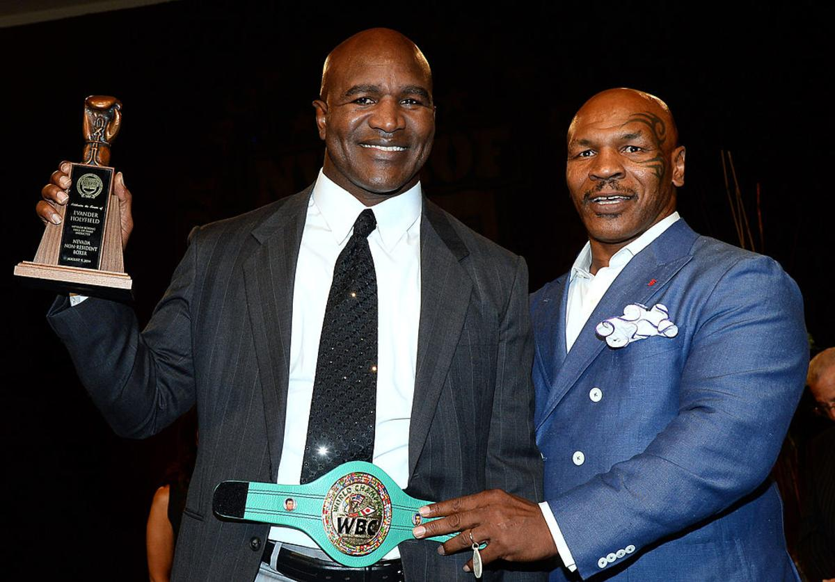 Former boxer Evander Holyfield (L) is inducted into the Nevada Boxing Hall of Fame by former boxer Mike Tyson at the second annual induction gala at the New Tropicana Las Vegas on August 9, 2014 in Las Vegas, Nevada