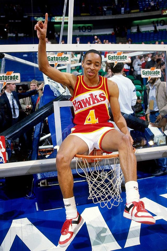 Spud Webb #4 of the Atlanta Hawks poses as he sits on top of the basket pointing in the air after winning the 1986 Slam Dunk Contest on February 8, 1986 at Reunion Arena in Dallas, Texas.