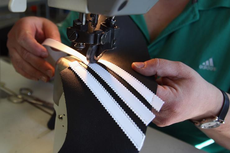 Employee Andrea Erbshaeuser stitches the three stripes on a football boot at the factory of German sporting-goods maker Adidas AG on February 23, 2011 in Scheinfeld, Germany. The world's second biggest sports equipment and clothing maker, adidas, will present its 2010 result during a press conference on March 2, 2011.